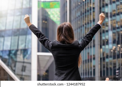 Successful business woman concept: woman in corporate outfit cheers with raised arms in front of modern office buildings