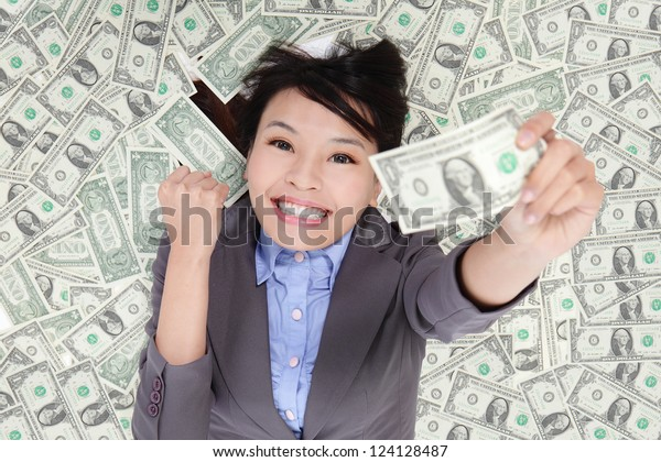 successful business woman hold fist with money and lying on money bed, asian beauty model