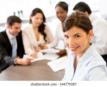 Successful business woman at the office with her team