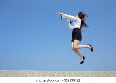 Successful business woman shouting in megaphone with blue sky background, full length, asian