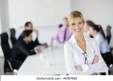 Successful business woman standing with her staff in background at modern bright office