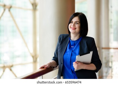 Successful business woman working with computer and tablet.