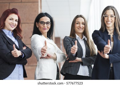 Successful business women with thumbs up and smiling