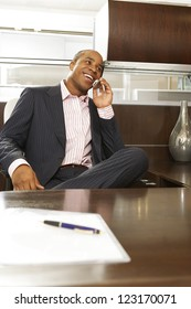 Successful businessman of African descent relaxing in the chair behind his desk talking on his mobile phone