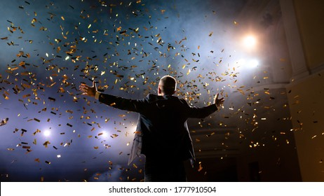 Successful businessman with arms up celebrating his victory. Celebrating success. Low angle view of excited young businessman keeping arms raised and expressing positivity while stands on the stage