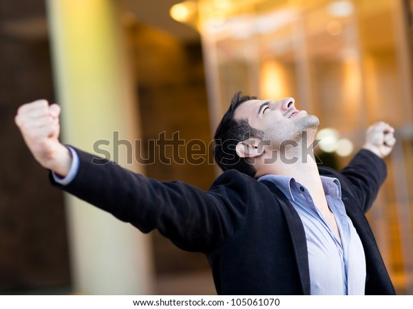 Successful businessman with arms up celebrating his victory