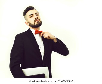Successful businessman with beard and arrogant face expression checks his red bow tie and holds computer, isolated on white background, copy space. Idea of confidence