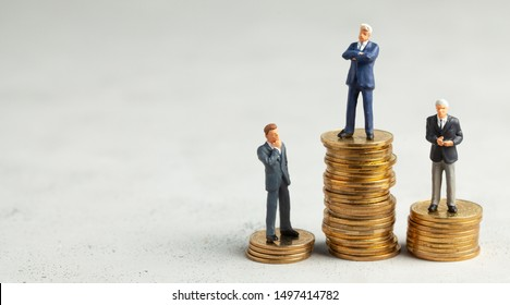 Successful businessman with big profits on stack of gold coins and less successful businessmen with small companies. The concept of how to learn to earn more, learning business