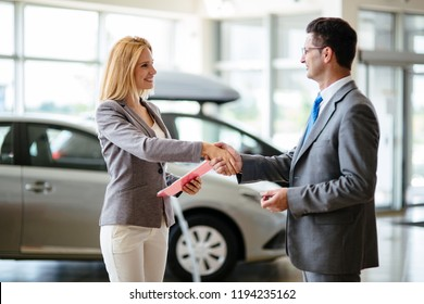 Successful businessman in a car dealership - sale of vehicles to customers