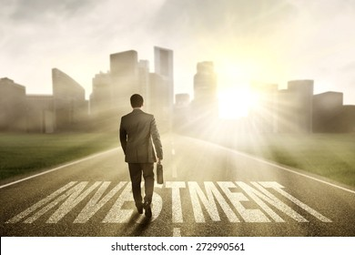 Successful businessman carrying a briefcase and walk on the road with an investment text