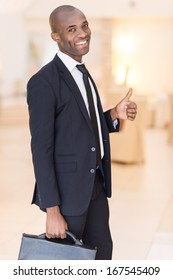 Successful businessman. Cheerful young African man in formalwear holding a briefcase and gesturing while smiling at camera