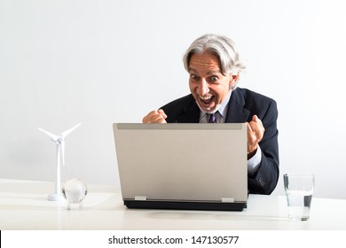successful businessman cheering behind his laptop in a modern bright office. The white desk is decorated with the model of a wind turbine and a globe that can easily be removed if not needed