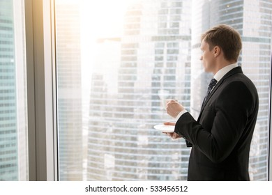 Successful businessman in classical formal suit standing in office, looking through window at big city skyscrapers, drinking coffee, dreaming of future, thinking of new deals. Copy space for text