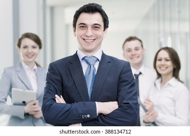 Successful businessman with colleagues in the background