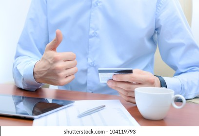 Successful businessman with a credit card in hand, sits at the workplace.