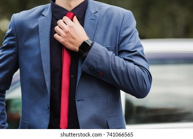 Successful businessman in a dark business suit with a red tie against the background of a car. Stylish man. Fashionable watch on hand. To correct a tie