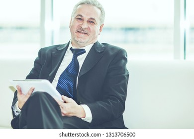 successful businessman with digital tablet sitting on sofa in the office.
