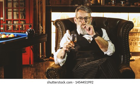 Successful businessman enjoys smoking a cigar in the men's club