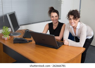 Successful businessman explaining something to his pretty colleague while they looking at monitor