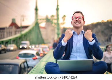 Successful businessman exulting. He is sitting on a bridge, in the middle of a trafficated street, using a laptop.