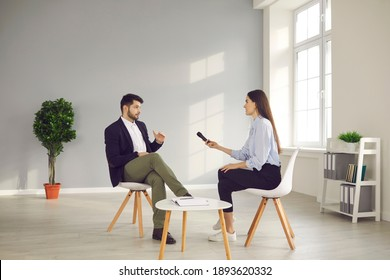 Successful businessman or famous politician giving interview and sharing opinion with newspaper journalist. TV host with microphone asking young male celebrity questions in television talk show studio - Shutterstock ID 1893620332