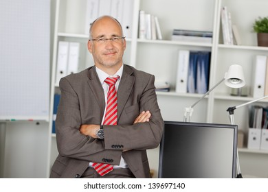 successful businessman with folded arms leaning on desk
