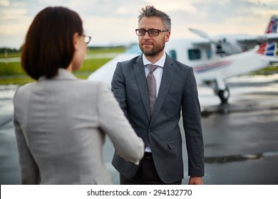 Successful businessman greeting his partner by handshake on background of airplane
