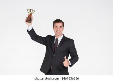 Successful Businessman handsome wearing a suit  with tie Glad to win the business competition and thumb up  hold gold words .