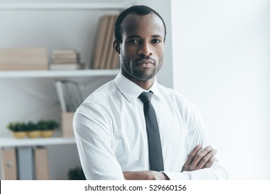 Successful businessman. Handsome young African man keeping arms crossed and looking at camera while standing in creative office