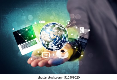 A successful businessman has control over the world concept holding planet earth, laptop in his hand with graph curves in the background. Elements of this image furnished by NASA.