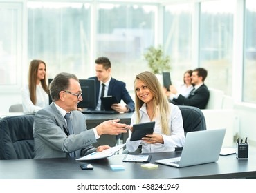 successful businessman and his assistant discuss the work plan of the company in a modern office