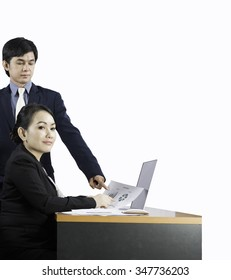 Successful businessman and his pretty colleague looking at monitor of computer