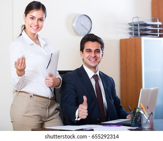 Successful businessman and his young attractive assistant smiling in modern office