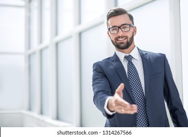 successful businessman holding out his hand for a handshake