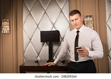 successful businessman holding a smartphone.  handsome man is typing a message on phone