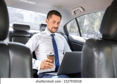 Successful businessman with laptop drinking coffee in modern car