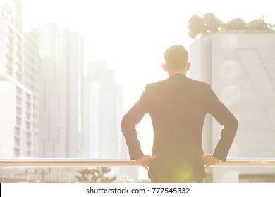 Successful businessman looking to the future on terrace in the sun shine morning on modern office city background with copy space area. Business success, victory, freedom, happiness, relax concept