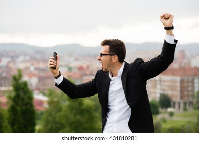 Successful businessman looking his smartphone. Young casual entrepreneur celebrating business success or good news.