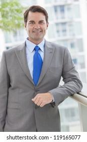 Successful businessman  or man in a suit on roof of a corporate skyscraper office building