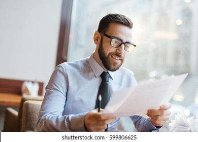 Successful businessman reading papers in cafe