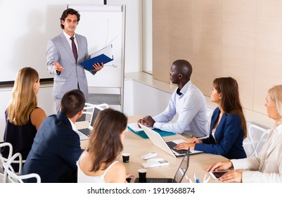Successful businessman sharing business ideas with colleagues in meeting room. Concept of teamwork