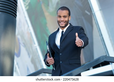 A successful businessman showing thumb up. Confident African businessman holding a laptop and goes down and smiling looking at the camera