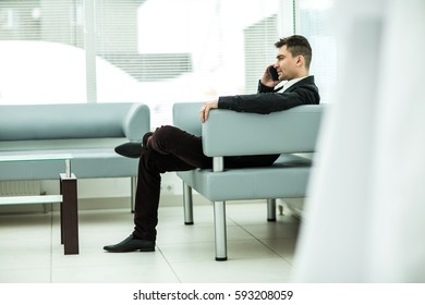 successful businessman sits in the lobby of a modern office