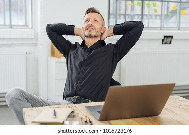 Successful businessman sitting pondering a problem or new idea relaxing back in his chair at the office with his hands behind his head