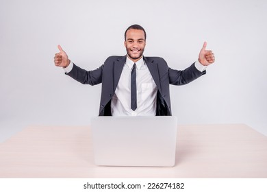 successful businessman. Smiling African businessman sitting at a desk on a laptop while businessman sitting at the table and showing thumb up over a laptop isolated on a gray background