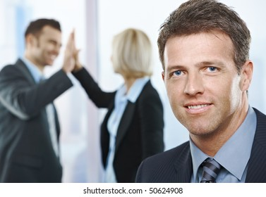 Successful businessman smiling at camera, with coworkers clapping hands together in background.