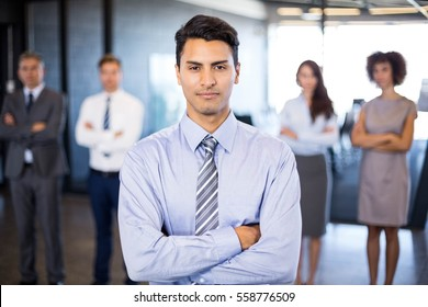 Successful businessman smiling at camera while her colleagues standing behind him in office