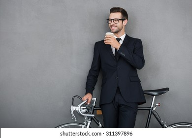 Successful businessman. Smiling young man leaning at his bicycle and holding cup of coffee while standing against grey background