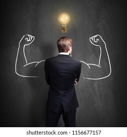 successful businessman standing in front of a blackboard with a bright lightbulb over his head