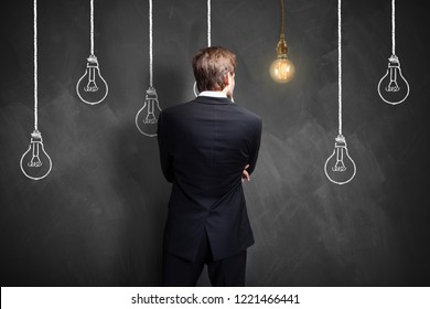 successful businessman standing in front of a blackboard with lightbulbs, symbolizing having an idea